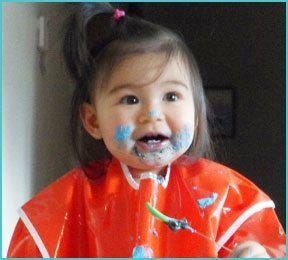 little girl with orange smock and blue pain on her face