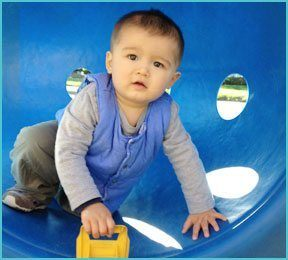 little boy with toy outdoors in blue plastic play equipment with holes